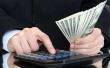 Мужчина высчитывает премию на калькуляторе и держит деньги